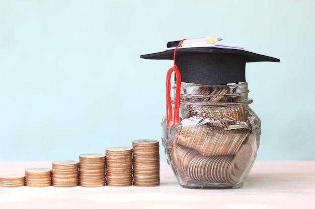 Chapéu graduação, ligado, moedas dinheiro, em, a, garrafa vidro, branco, fundo Foto Premium