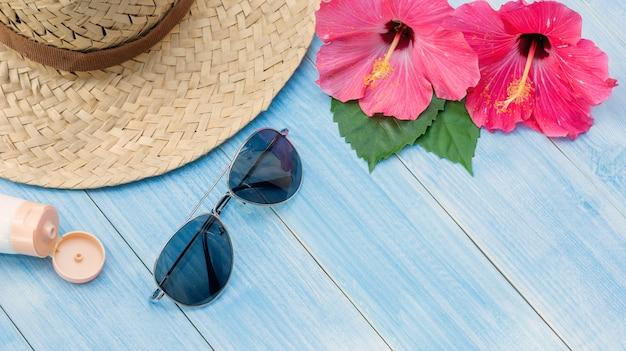 Chapéu, óculos de sol, protetor solar e chinês rosa flor sobre uma mesa de madeira azul. Foto Premium
