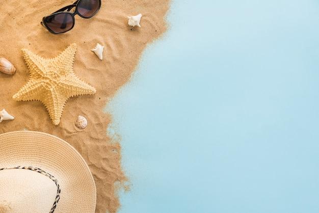 Chapéu perto de óculos escuros e conchas na areia Foto gratuita