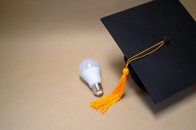 Chapéu preto da graduação colocado no papel marrom Foto Premium