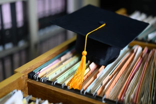Chapéu preto da graduação e borla amarela coloc no armário Foto Premium