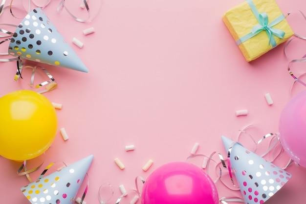 Chapéus de aniversário, bolas cor de rosa, amarelas, caixa de presente amarela e serpentina de prata sobre um fundo rosa. fundo de férias. Foto Premium