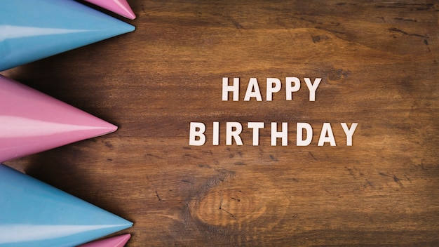 Chapéus de festa e escrita de feliz aniversario Foto gratuita