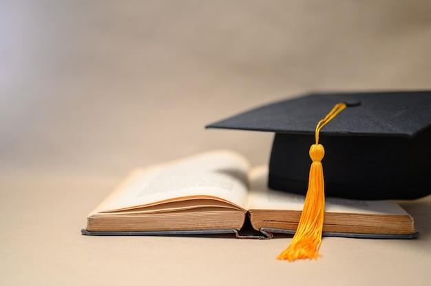 Chapéus de formatura preto colocados em livros abertos Foto Premium