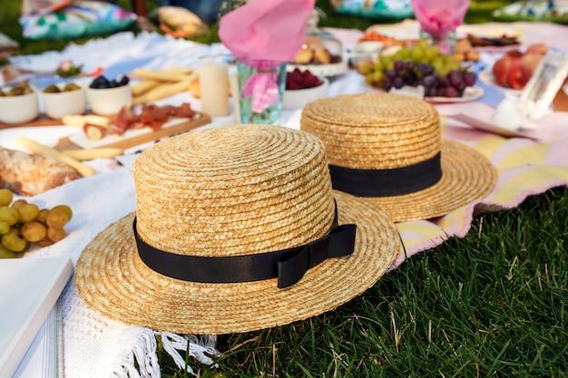 Chapéus de palha colocar em um cobertor de piquenique branco no gramado verde brilhante dia de verão Foto Premium