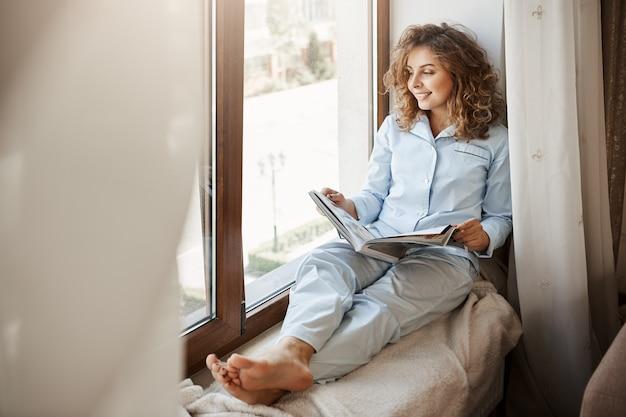 Charmosa empresária tendo tempo de relaxamento em casa. prazer mulher adulta bonita em roupa de dormir sentado no peitoril da janela e olhando para a rua, segurando a revista de moda, lendo sobre estilo de vida Foto gratuita