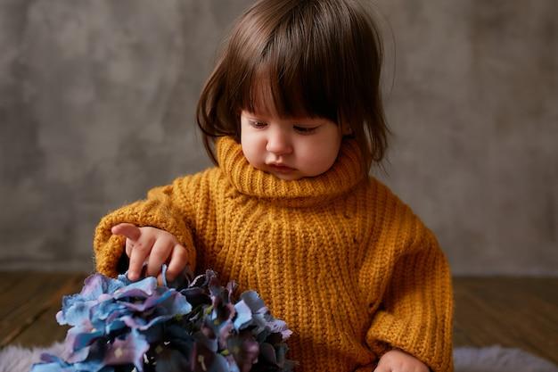 Charmoso bebê-menina em camisola laranja explora hortênsias azuis sentado no cobertor quente Foto gratuita