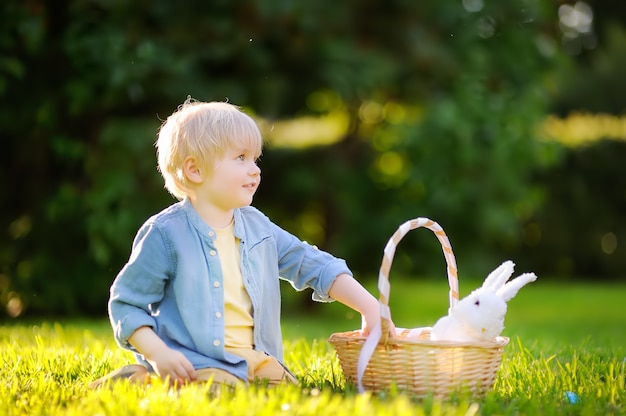 Charmoso rapaz caçando ovo de páscoa no parque primavera no dia de páscoa Foto Premium