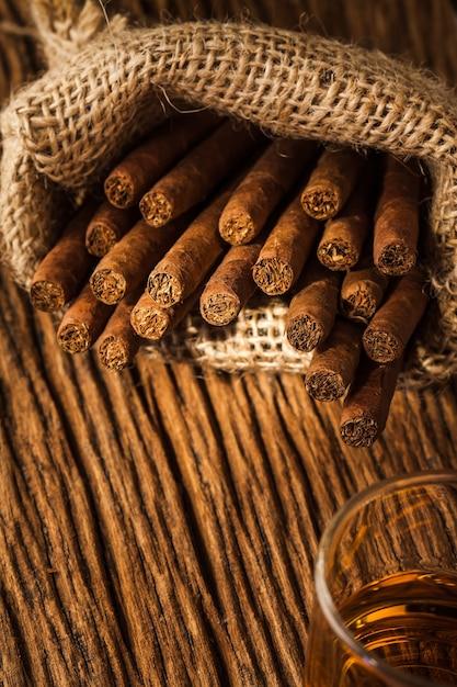 Charuto em saco pequeno na velha mesa de madeira Foto Premium