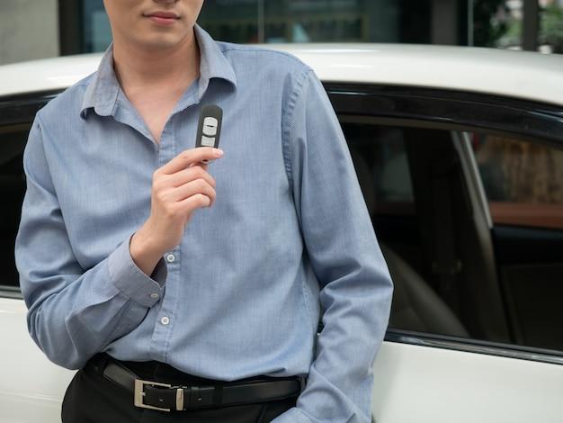 Chave da exploração do homem na concessionária de automóveis moderna. feche a mão do cardealer dando a chave do carro para o cliente Foto Premium