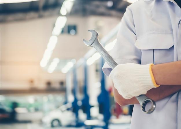 Chave de ferramenta é realizada por um reparador mecânico com serviço de reparo automático no centro de serviço. Foto Premium