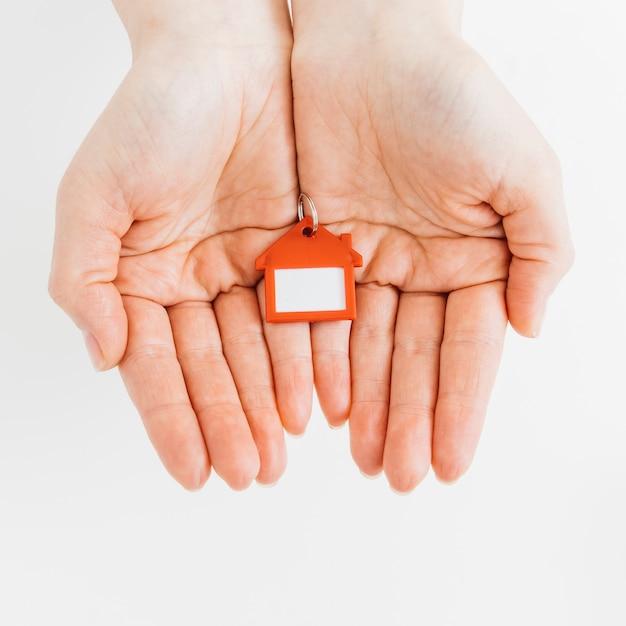 Chaveiro de forma de casa em mãos femininas contra fundo branco Foto gratuita