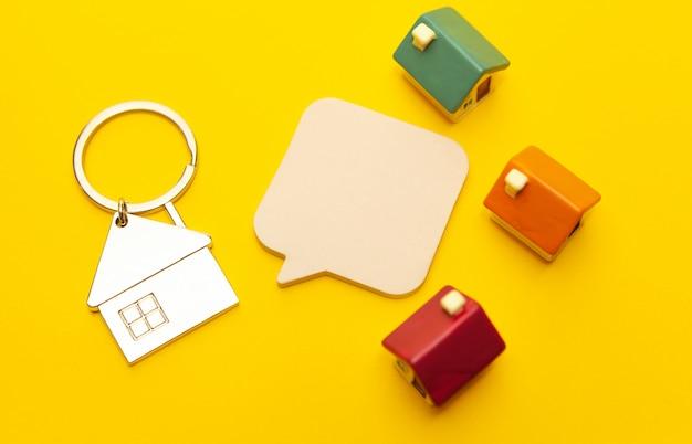 Chaveiro na forma de uma casa e casas de brinquedos em um fundo amarelo Foto Premium