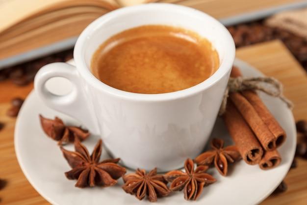 Chávena de café branco, cercado por grãos de café torrados Foto Premium