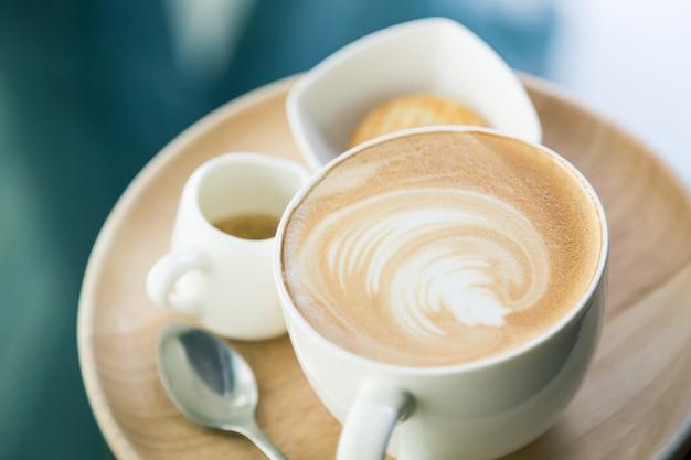 Chávena de café com uma bacia com bolinhos e uma colher de chá Foto gratuita