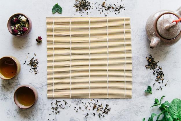 Chávenas de cerâmica tradicionais; bule de chá; flor seca e folhas secas ao redor do placemat Foto gratuita