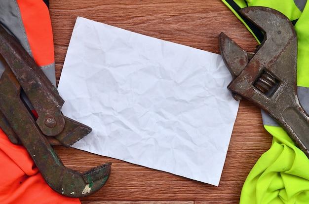 Chaves ajustáveis e mentiras de papel de camisas de um trabalhador do sinal da laranja e do verde Foto Premium