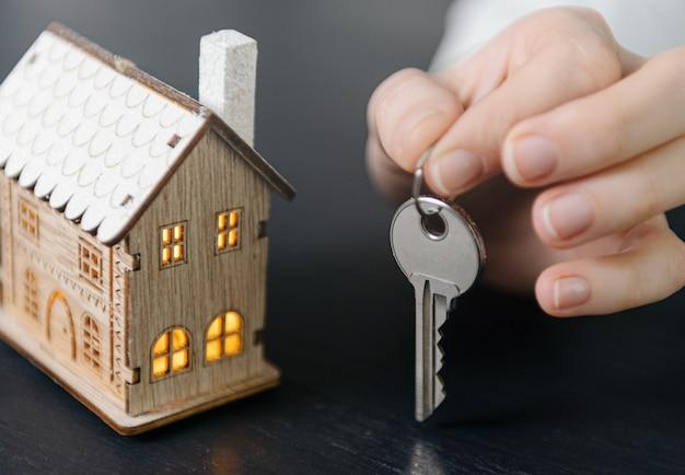 Chaves da casa nas mãos de uma mulher e um pequeno modelo de uma casa com janelas luminosas nas proximidades. conceito de adquirir sua casa Foto Premium