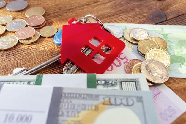 Chaves de casas vermelhas em miniatura nas notas e moedas Foto Premium