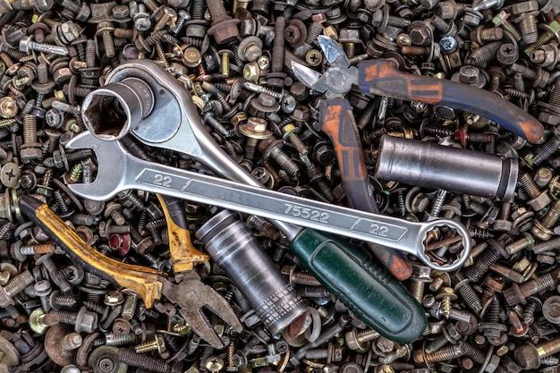 Chaves de metal plana lay, catraca, alicate, cabeças de ferramentas intercambiáveis de tamanhos diferentes estão no fundo de várias rodas dentadas de metal, parafusos e pregos, vista superior. Foto Premium