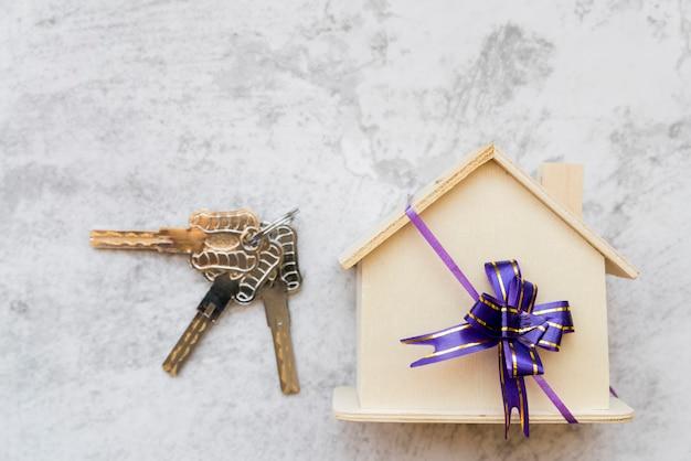 Chaves de prata perto da casa modelo de madeira com laço de fita na parede de concreto branco Foto gratuita