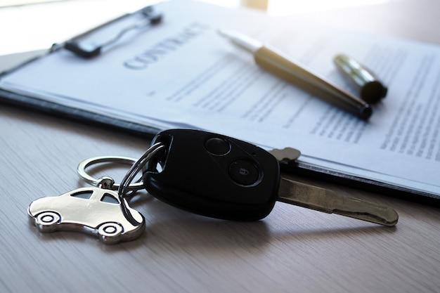 Chaves do carro colocadas em documentos do contrato sobre empréstimos de carro. Foto Premium