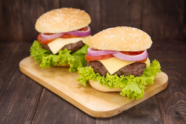 Cheeseburger em pães com carne suculenta no fundo de madeira Foto Premium