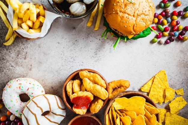 Cheeseburgers, batatas fritas, nachos, rosquinhas, refrigerantes e pepitas Foto Premium