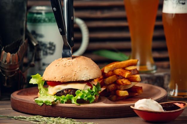Cheeseburguer clássico com batatas fritas e cerveja Foto gratuita