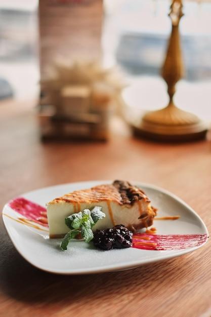 Cheesecake de mirtilo delicioso e doce no prato branco servido com chantilly Foto Premium