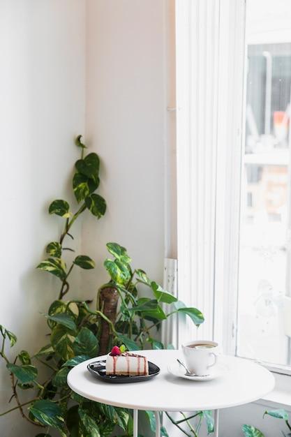 Cheesecake e xícara de café na mesa perto do golden pothos ou epipremnum aureum planta Foto gratuita