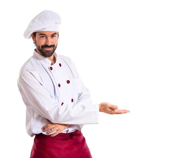 Chef apresentando algo sobre fundo branco Foto gratuita