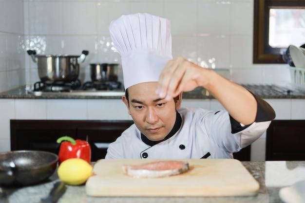 Chef asiático homem cozinhar alimentos no restaurante Foto Premium