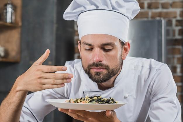 Chef bonito, cheirando o cheiro do prato cozido Foto gratuita