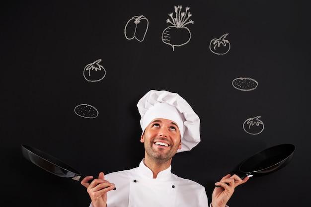 Chef bonito malabarismo com vegetais Foto gratuita