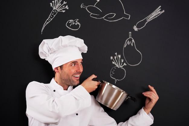 Chef bonito pegando ingredientes para a sopa Foto gratuita