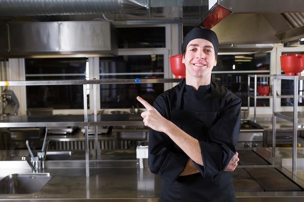 Chef com uniforme em uma cozinha Foto gratuita