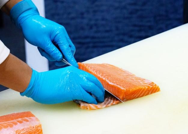 Chef, cortar salmão fresco cru, chef, preparando um salmão fresco em uma placa de corte Foto Premium