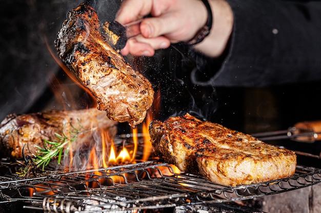 Chef cozinheiro frita carne, bife de vaca em uma fogueira em um restaurante Foto Premium