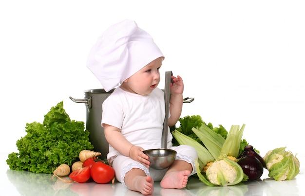 Chef de bebê fofo com panela grande e legumes Foto gratuita