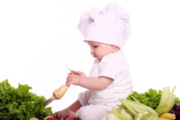 Chef de bebê fofo com vegetais diferentes Foto gratuita