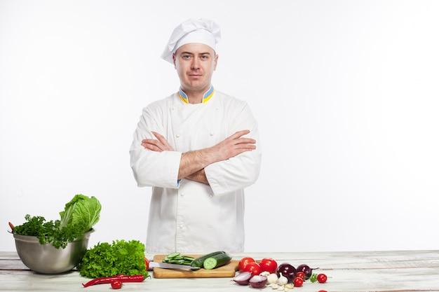 Chef de cozinha salada de legumes frescos em sua cozinha Foto gratuita