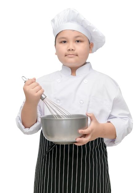 Chef de criança mantenha batedor com chapéu de cozinheiro e avental Foto Premium
