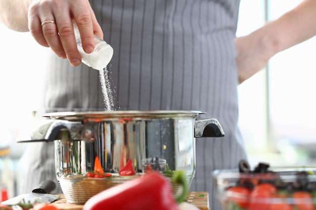 Chef de culinária adicionando sal marinho branco à panela Foto Premium