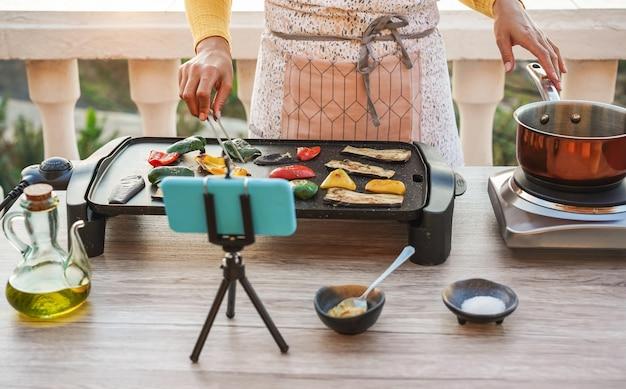 Chef de jovem mulher que cozinha ao ar livre durante o streaming on-line para a lição de masterclass de webinar em casa Foto Premium