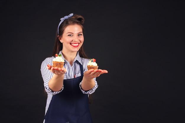 Chef de pastelaria com kopkeykami nas mãos de sorrisos para a câmera no estúdio em um fundo preto Foto Premium