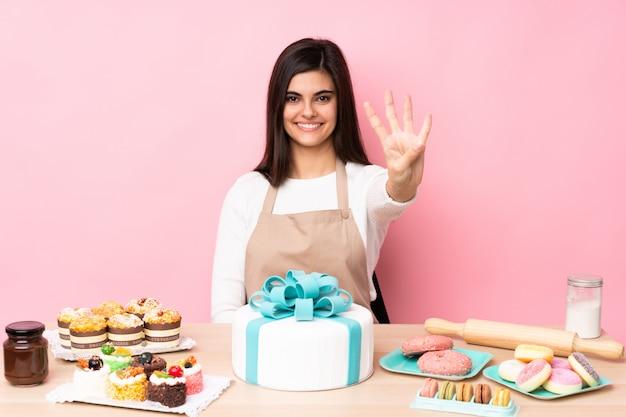 Chef de pastelaria com um bolo grande em uma mesa na parede rosa feliz e contando quatro com os dedos Foto Premium