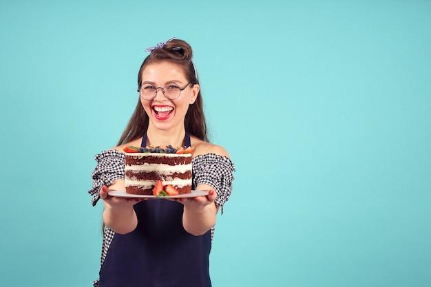 Chef de pastelaria feliz posando para a câmera com um bolo nas mãos Foto Premium