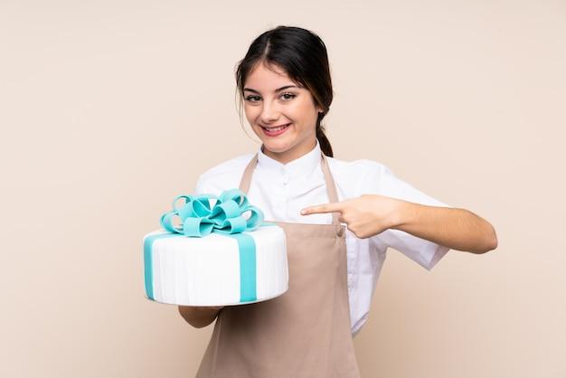 Chef de pastelaria mulher segurando um bolo grande e apontando-o Foto Premium
