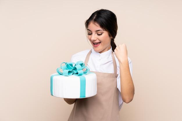 Chef de pastelaria mulher segurando um bolo grande sobre parede isolada comemorando uma vitória Foto Premium